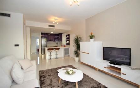 Vardagsrum med öppet kök i lägenhet med 2 sovrum