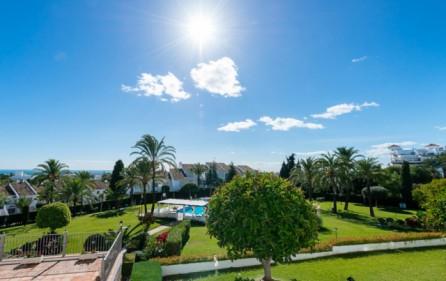 Utsikt mot hav och trädgård från terrass