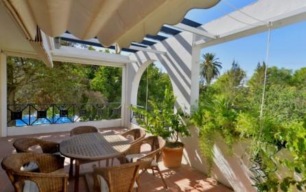 Terrassen med utsikt mot pool och trädgård